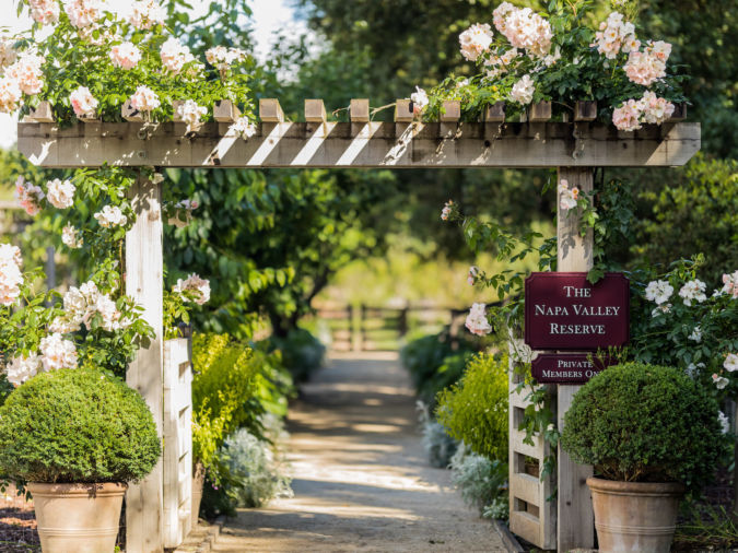 Napa Valley Reserve wine club entrance with beautiful pink flowers above a wooden frame