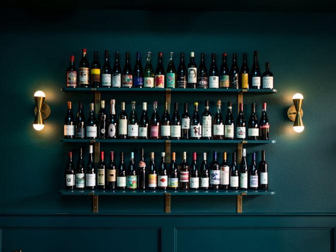 three shelves displaying various bottles of high end wine