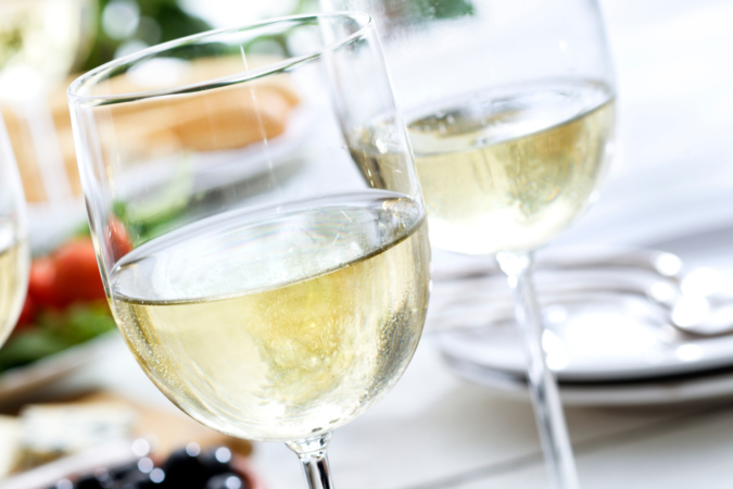 three clear wine glasses filled with white wine