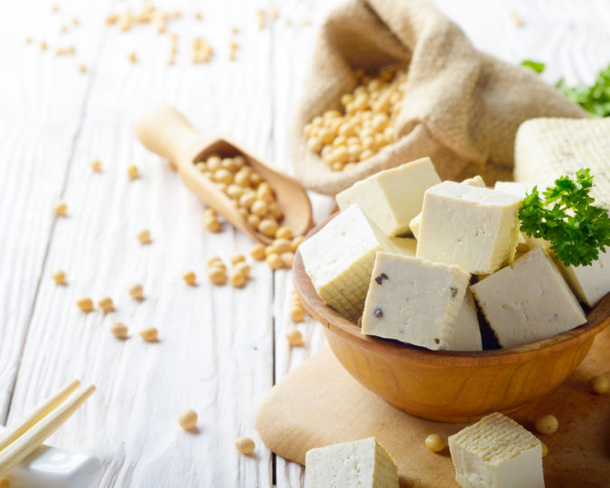 Soy Bean cuSoy Bean curd tofu in wooden bowl and in hemp sack on white wooden kitchen table. Non-dairy alternative substitute for cheese. Place for textrd tofu in wooden bowl and in hemp sack on white wooden kitchen table. Non-dairy alternative substitute for cheese