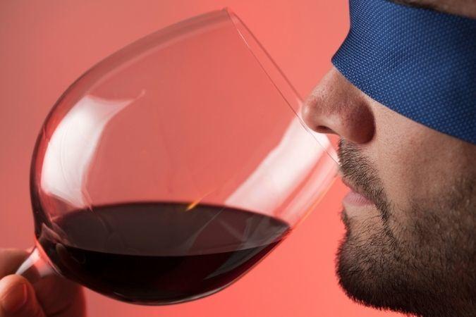 Man tasting wine wearing a blindfold