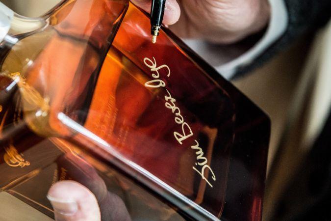Jim Beveridge signing a whisky bottle