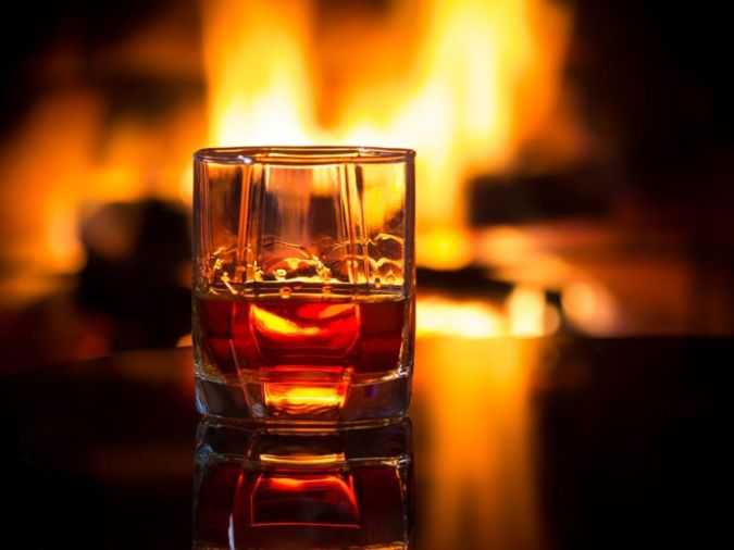 Glass of whisky next to an open fire