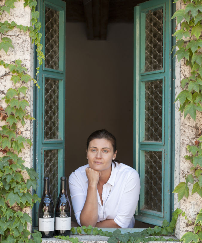 Gaia Gaja leaning out an ivy framed window with bottled wine