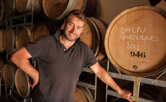 Mark Haisma smiling next to wine barrels