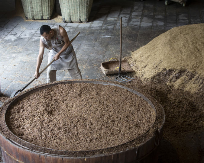A worker fills a steam vat with fermented grain at a baijiu production facility