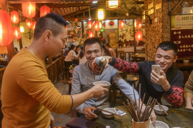 Young people drinking Baijiu in a restaurant local to China