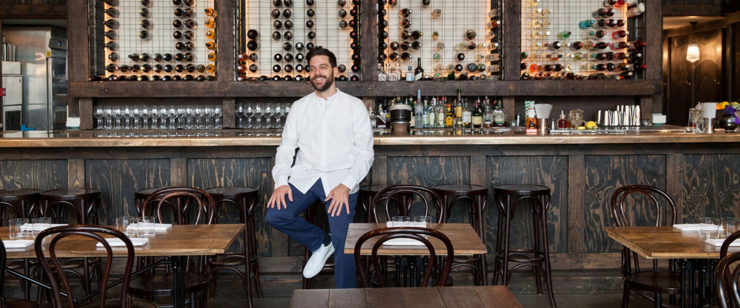 Michael Sager of Sager + Wilde sitting on a bar stool next to a wooden bar