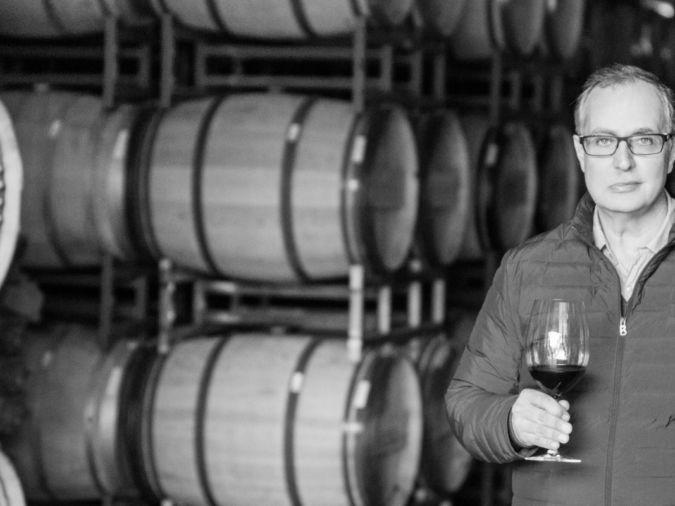Winemaker Daniel Daou standing in front of wine barrels