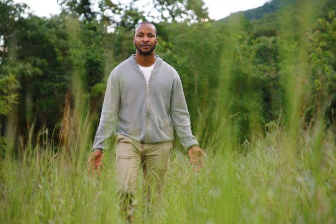 Sommelier Tinashe Nyamudoka posing in a field
