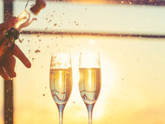 Champagne being opened and exploding with bubbles. There are also 2 champagne glasses.