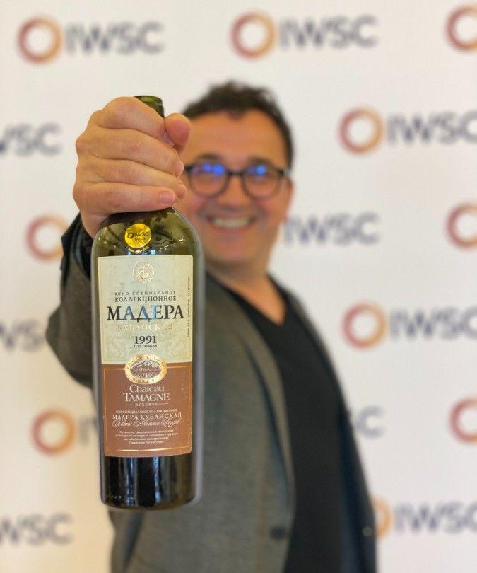 sommelier Igor Sotric holding wine bottle at IWSC judging