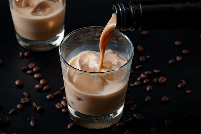 pouring cream liqueur into tumbler with ice