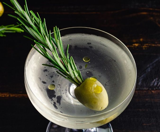 savoury gin martini with an olive and rosemary garnish