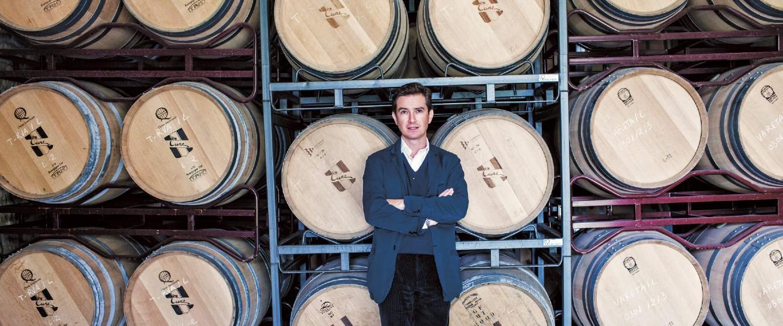 CVNE CEO victor Urrutia posing before barrels at the winery
